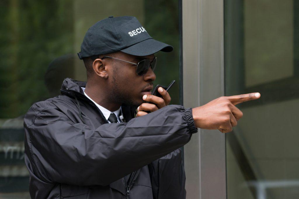 Male Security Guard Talking On Walkie-Talkie