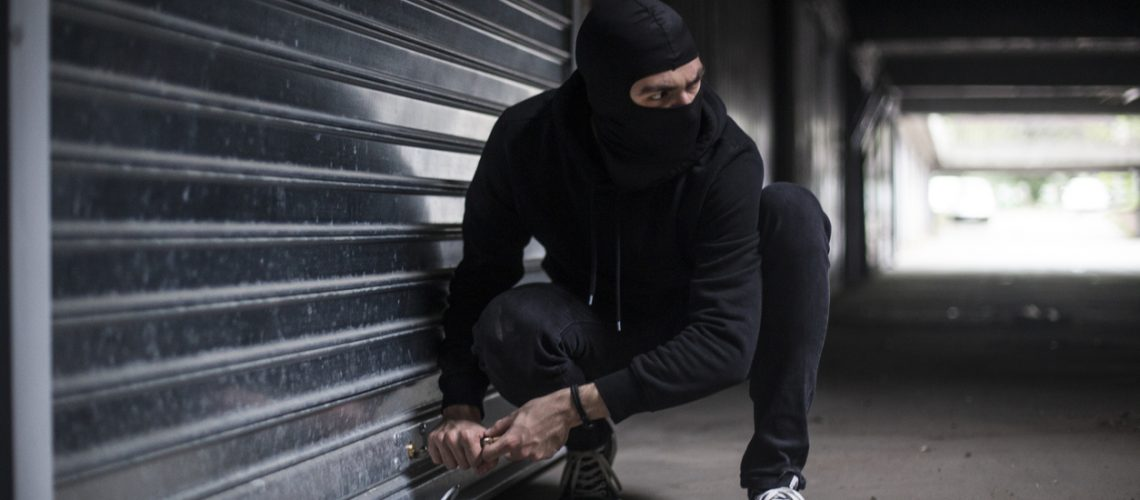 Burglar trying to rob a garage. Unrecognizable Caucasian male wearing a balaclava.